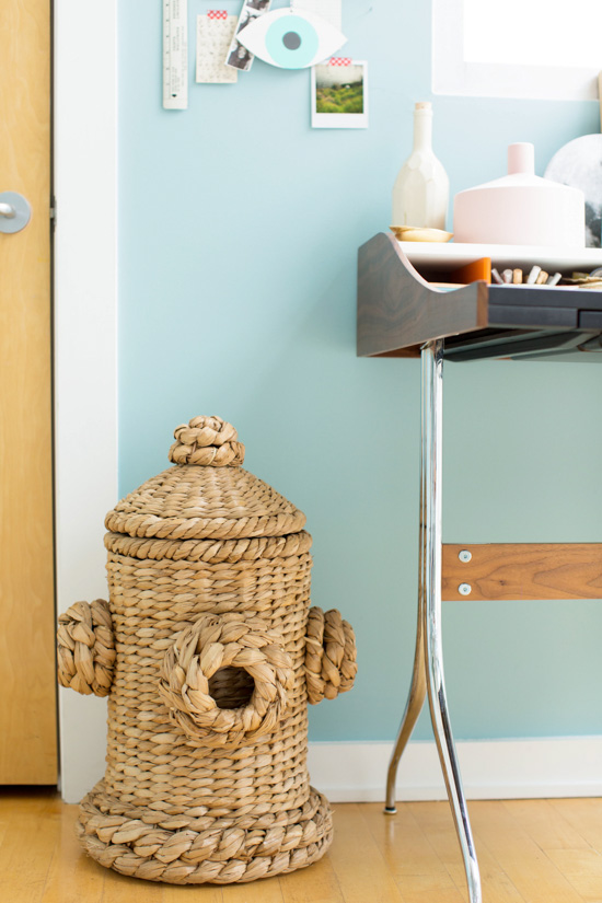 A wicker fire hydrant basket becomes a quirky trash can in this colorful modern workspace.