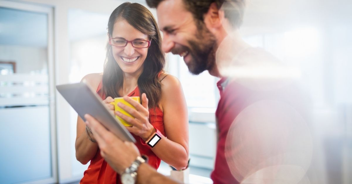Happy man and woman looking at a tablet