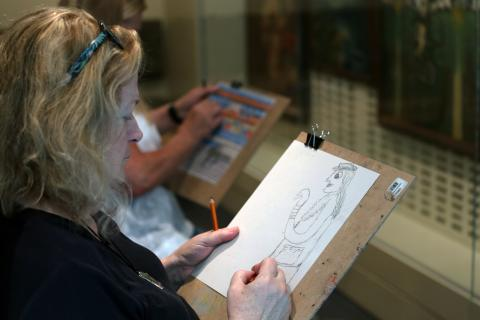 A photo of a woman sketching in the Luce Foundation Center at the Smithsonian American Art Museum.