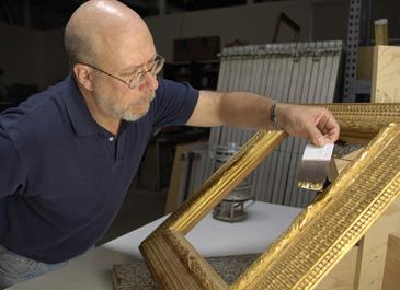 A conservator inspecting a frame of art at the Lunder Conservation Center
