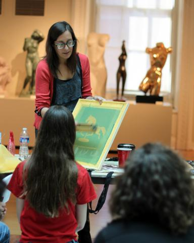 Artist demonstrating screen printing for visitors