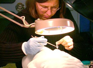 A conservator inspecting an object in the Lunder Conservation Center