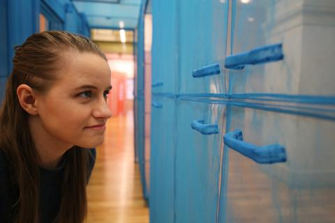 This is an image of a woman looking at the details of Do Ho Suh's work.