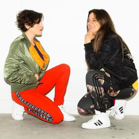 An image of two girls sitting on the floor looking at each other.