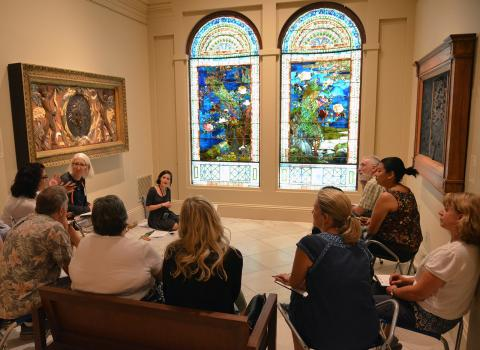 A group of teachers talking in front of a stained glass artwork.