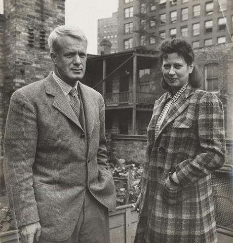 A photograph of a man and woman standing outside in coats.
