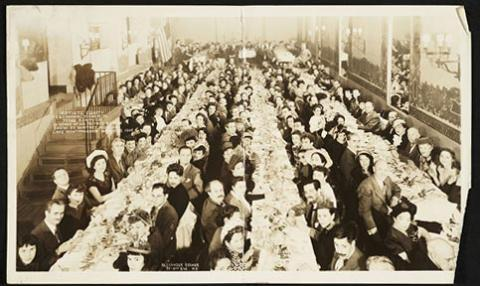 A photo of three long tables with people eating on each side.
