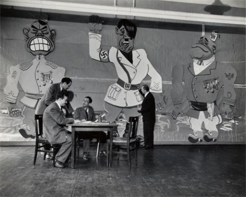 An image of men sitting at a table talking with a mural behind them.