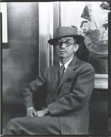 A picture of Yasuo Kuniyoshi in a suit and hat sitting in front of artwork.