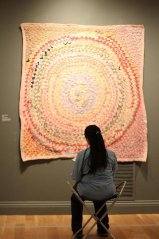 A woman sitting in front of a quilted artwork.