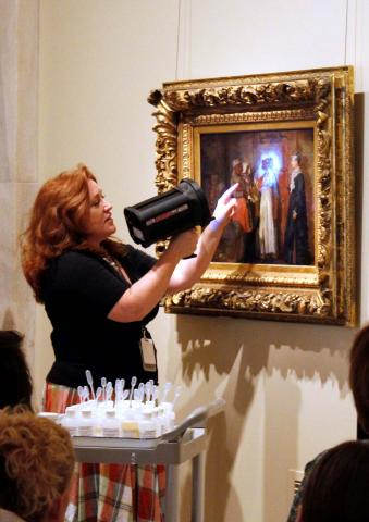 Conservator shining light on an artwork.