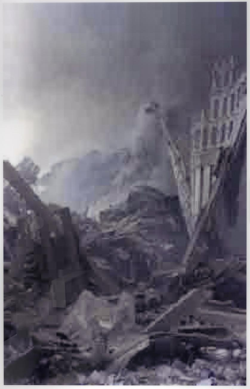 A pixelated photograph of a scene of a destroyed city. The image is in shades of gray.