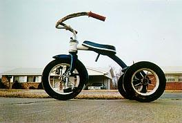 A photograph of a tricycle at a low angle
