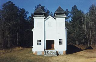 A painting of a white church in the woods
