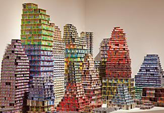 An installation of scratch & win lottery tickets stacked on top of one another forming structures.