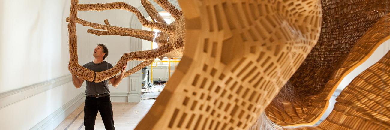 This is an image of John Grade installing Middle Fork for the WONDER exhibition at the Renwick Gallery.