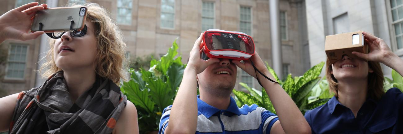 An image of three people playing the wonder360 app with different VR attachments to their smart phones.