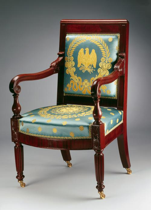 An image of a mahogany armchair with blue and gold upholstery