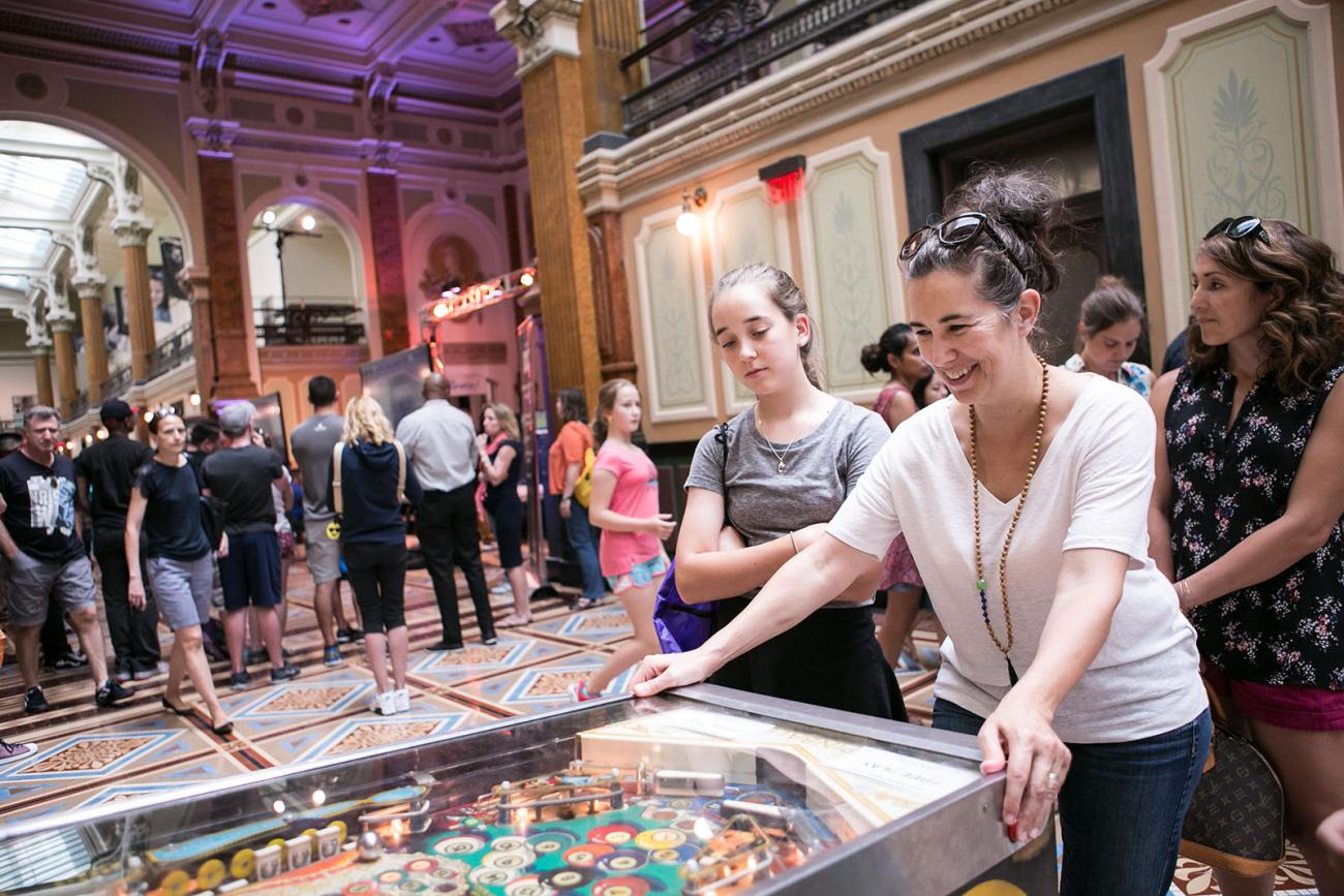 A photograph of a woman playing pinball inside the Smithsonian American Art Museum during SAAM Arcade.