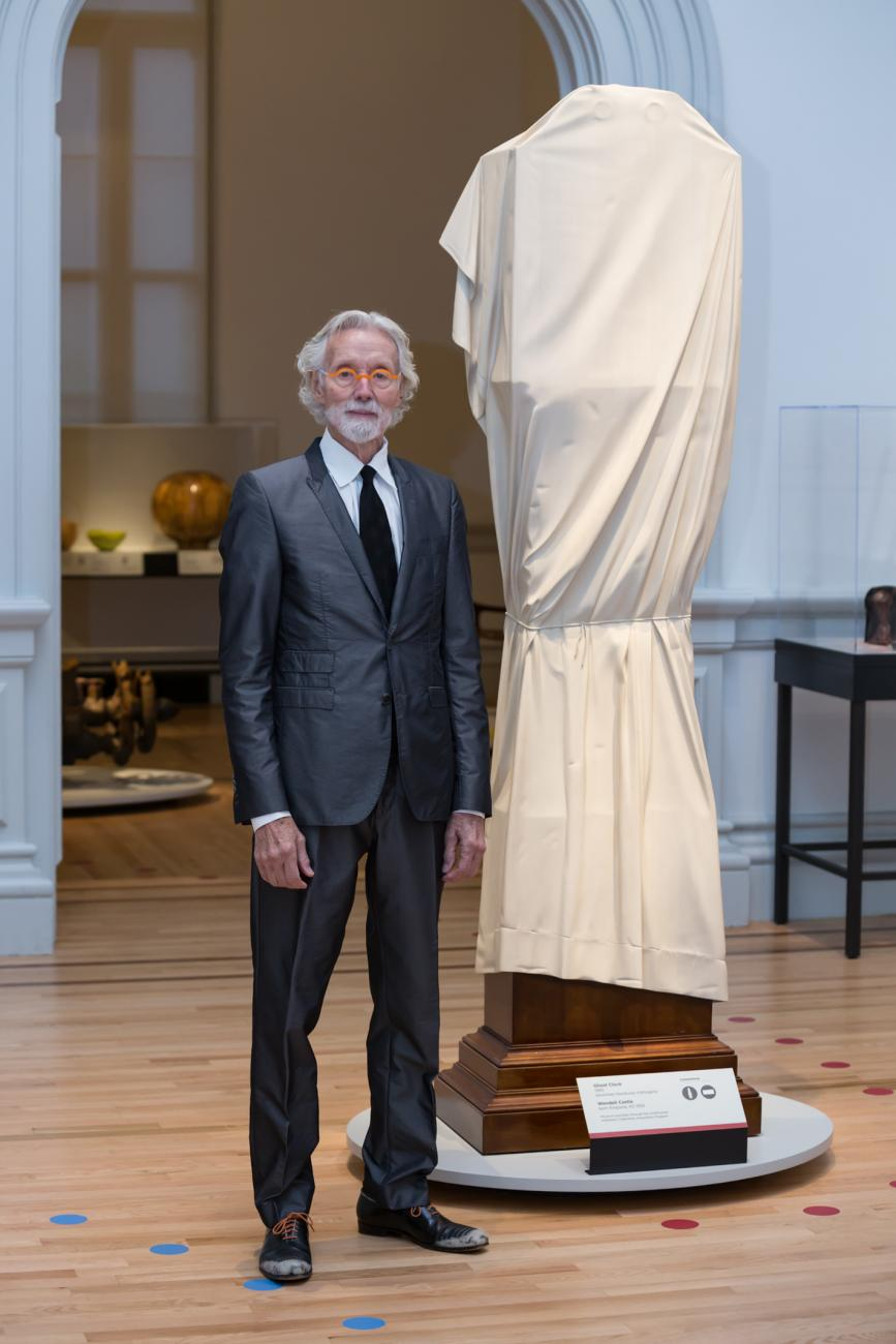 "This is a photo inside the Renwick Gallery of artist Wendell Castle standing next to ""Ghost Clock"""