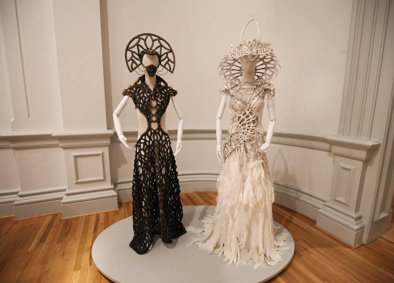 A photograph of two costumes for Burning Man at the Renwick Gallery.