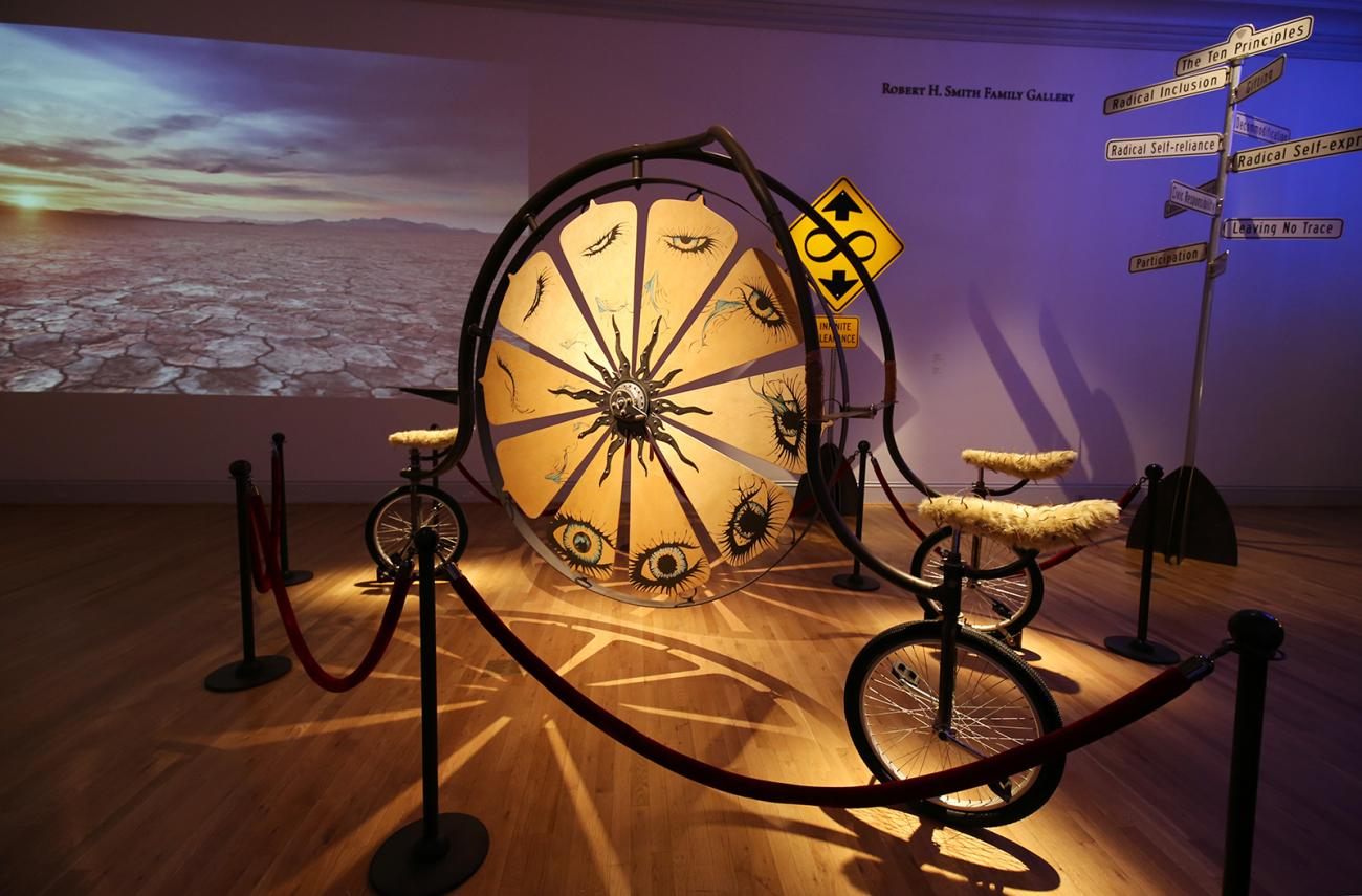 An image of a three man bike with a big wheel in the center that you can spin.