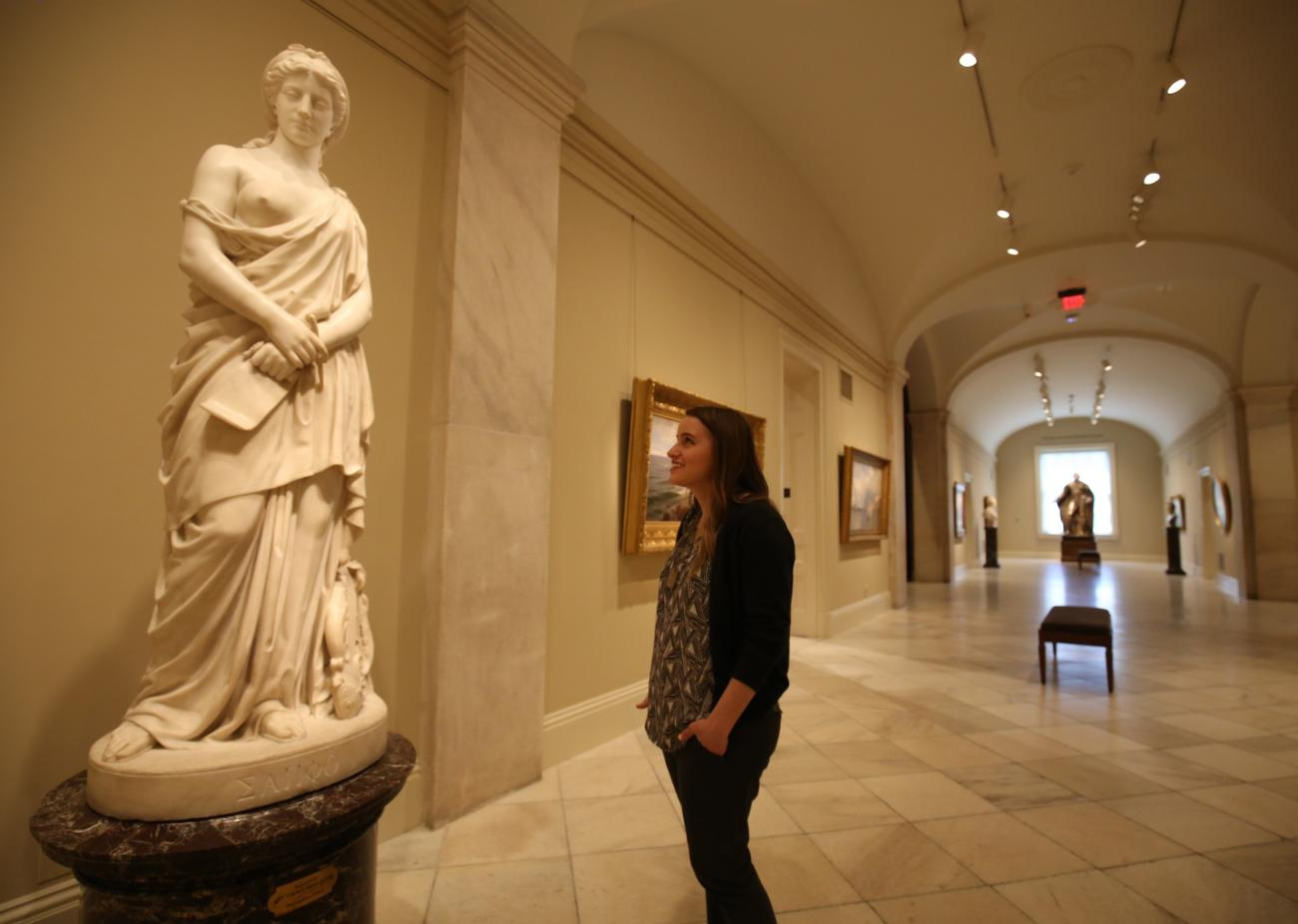 "A gallery shot of a figure looking at the sculpture ""Sappho"" by Vinnie Ream."