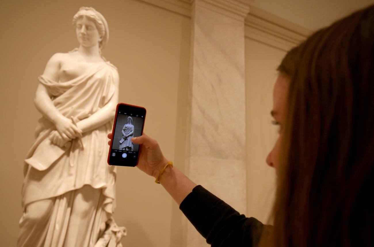 "An image of a visitor taking a picture of the sculpture ""Sappho"" by Vinnie Ream."