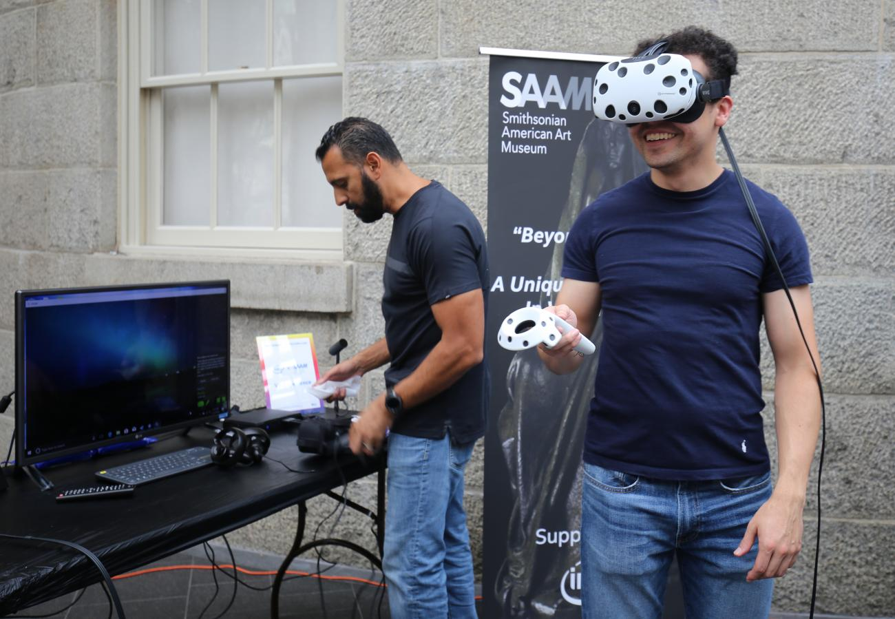 A photograph of a man with a VIVE headset on while playing a virtual reality game at the Smithsonian American Art Museum.