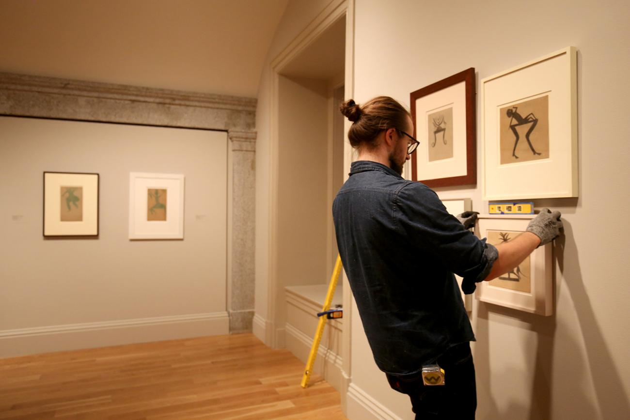 Photo of a man hanging pictures on a gallery wall and checking them with a level.