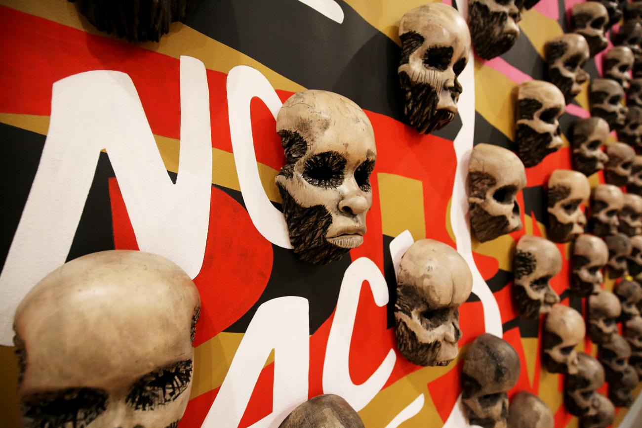 A detailed photograph of wood carved skulls on a wall.