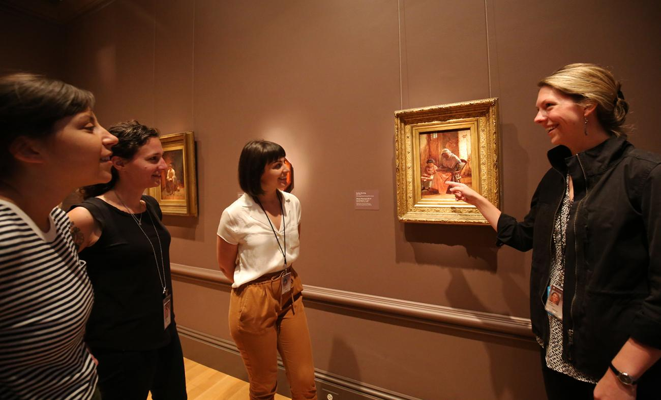 a photograph of four individuals looking at a work of art in a museum.