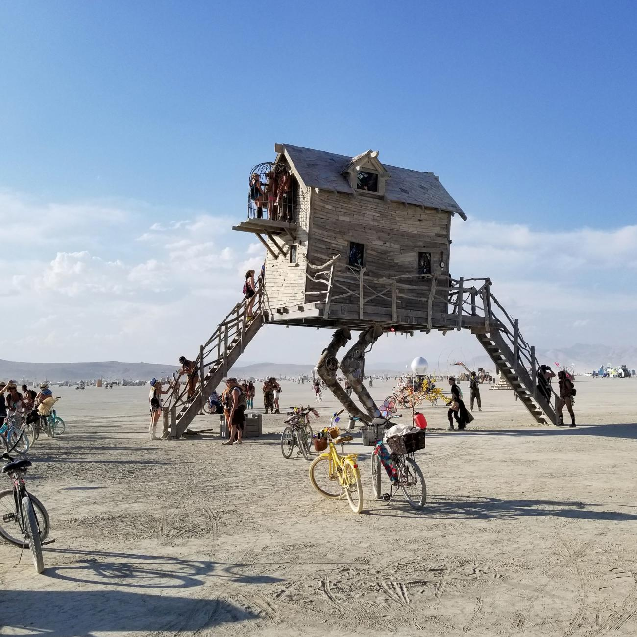 A photograph of a house with robot legs in the desert.