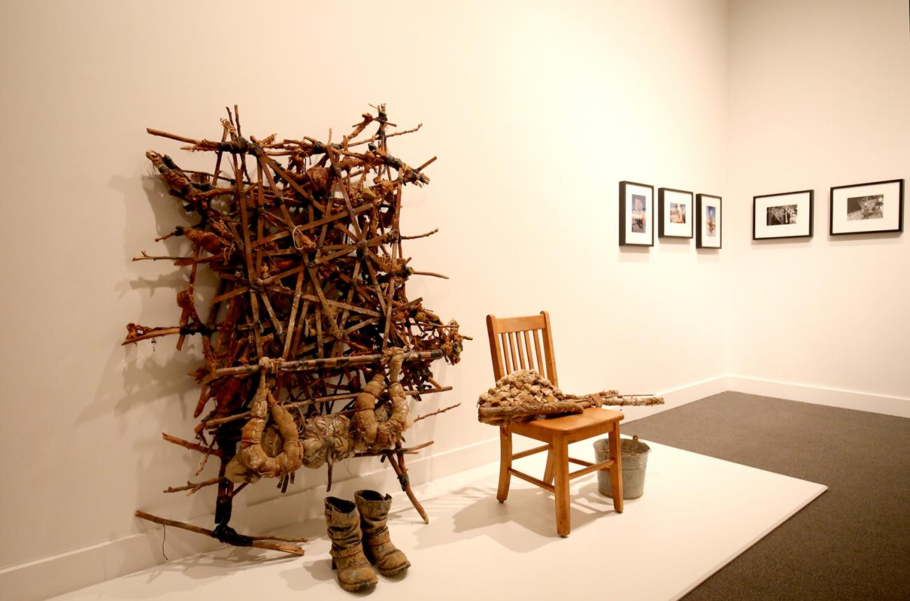 A photograph of artwork on a wall with a chair and combat boots.