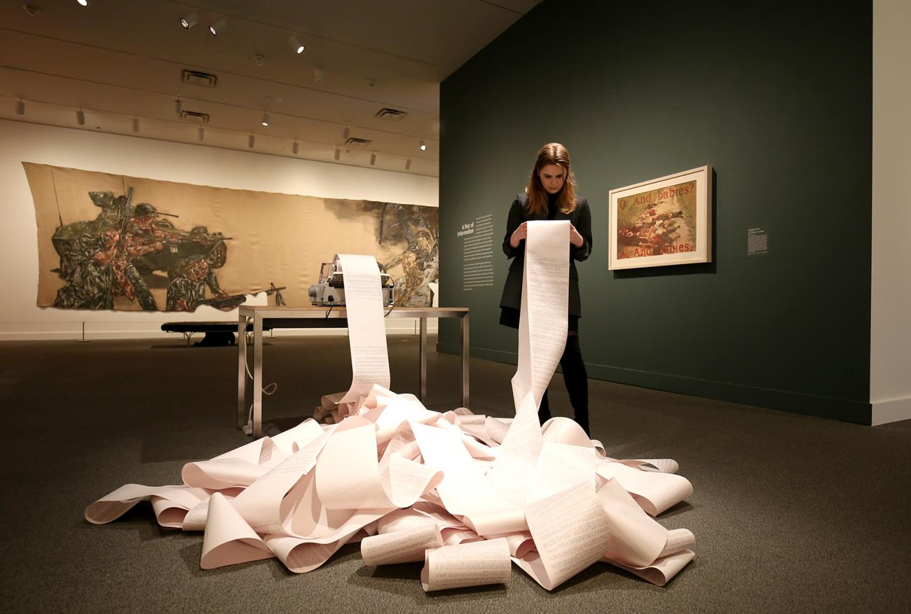 A woman looking at printed paper inside a gallery.