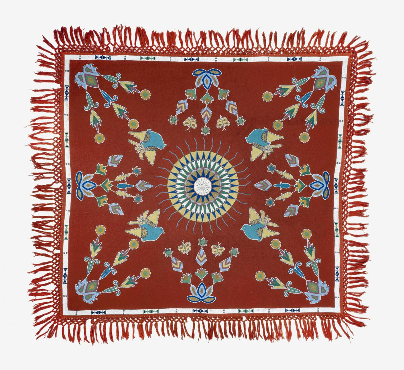 A red tablecloth with a circle in the middle and different designs around it.