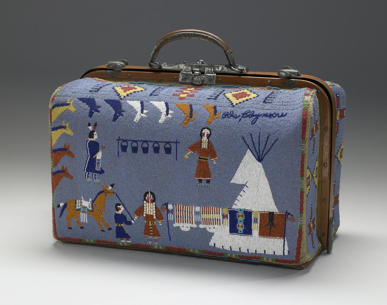 A blue suitcase made of beads with designs of people, a teepee, and animals.