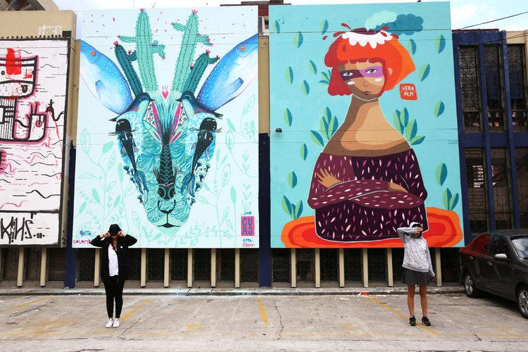 People stand in front of murals created by street artists
