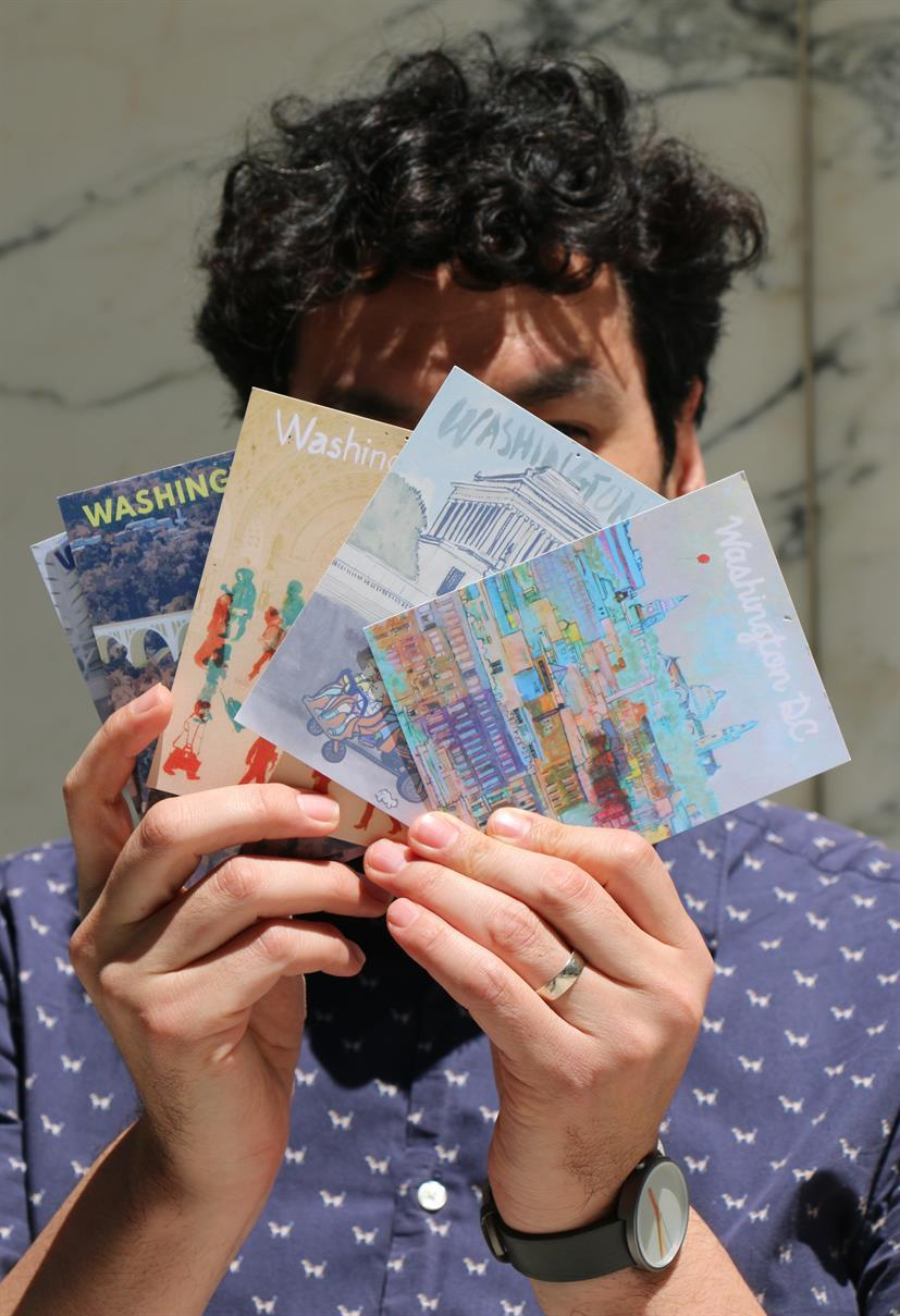 The artist holding some of his illustrated DC postcards