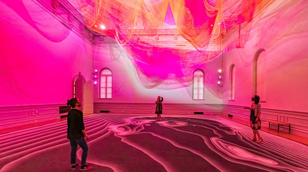 Three people looking up at an art installation inside the Renwick Gallery.