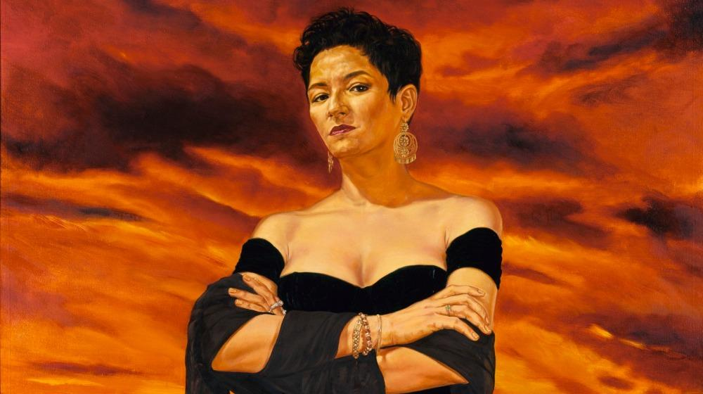Woman with her arms crossed with a sunset background.