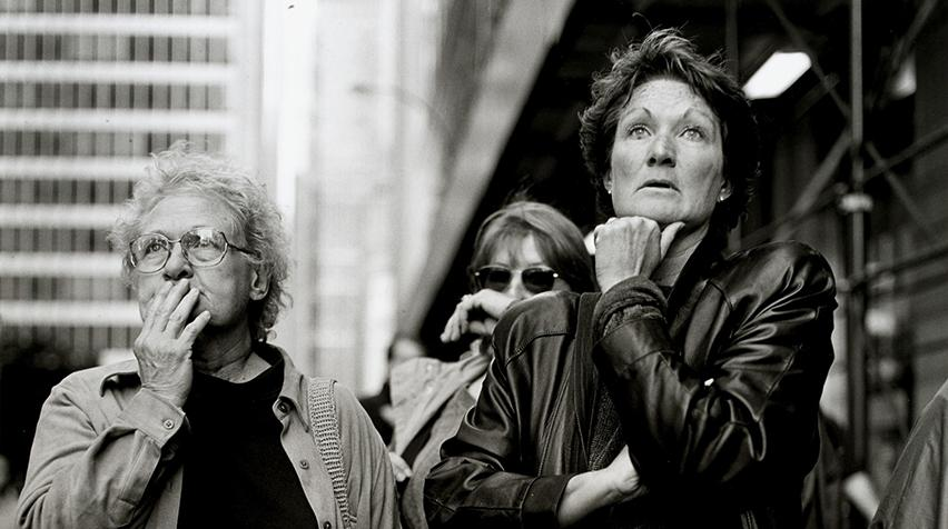 A black and white photograph of three women looking in the near distance with shocked looks on their faces