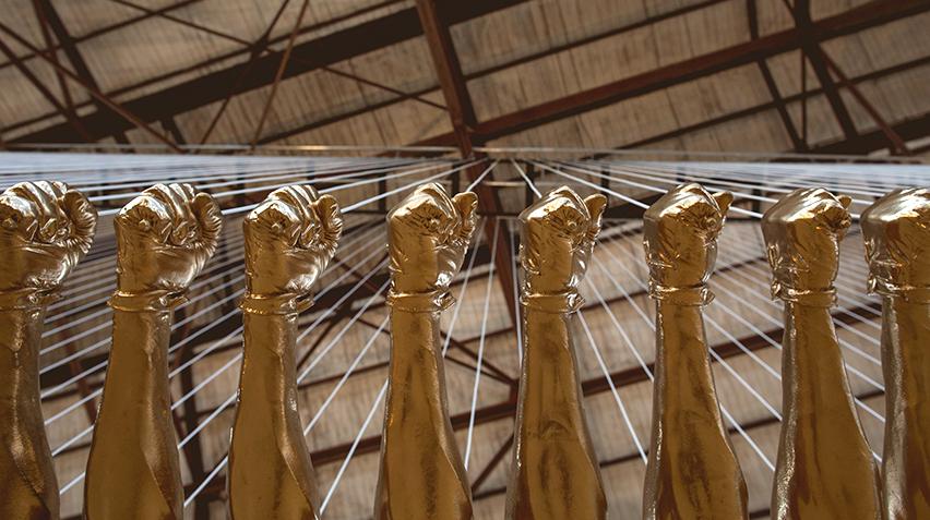 A detail of a sculpture of fiberglass fists painted gold