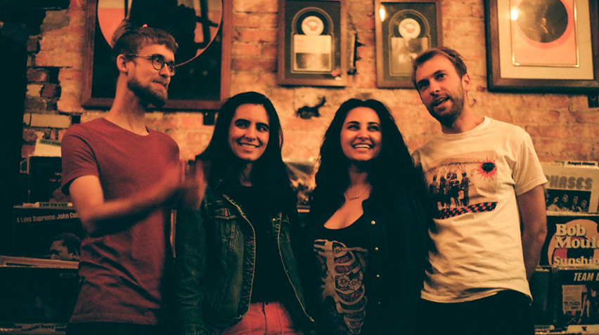 The four musicians of the band Rosie Cima and What She Dreamed stand with their arms around eachother in a room full of framed pictures.