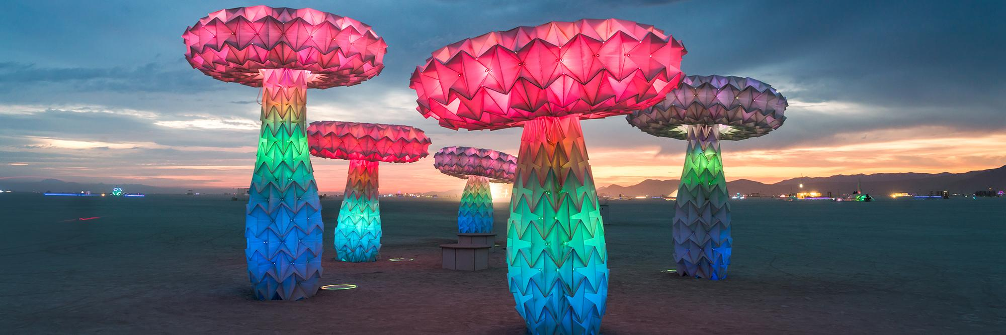 A photo of Shrumen Lumen, a faceted mushroom sculpture piece, installed in the desert at Burning Man 2017.