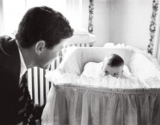 JFK looking into baby bassinet with baby Caroline peeking over the side