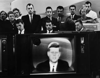 Group of people around a television set showing JFK on the screen