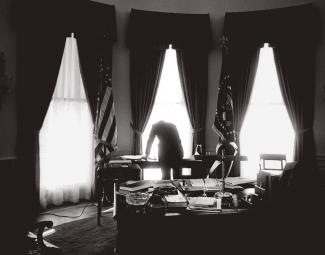Kennedy bending over in silhouette against the Oval Office windows