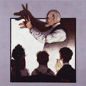 An image of a man making shadow puppets on the wall in the background and three children watching in the foreground.