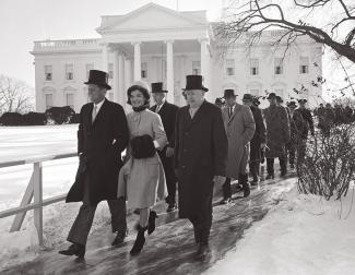Procession of people following JFK and Jackie through a snowy scene
